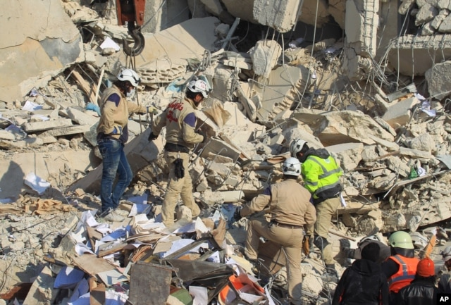 FILE - Civil defense members search for survivors at a site hit by what activists said were airstrikes carried out by the Russian air force in Idlib city, Syria, Dec. 21, 2015.
