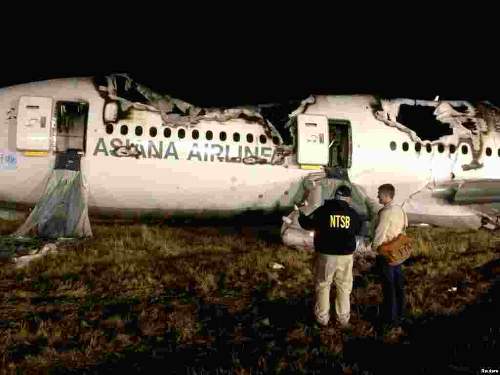 National Transportation Safety Board investigators assess the wreckage of Asiana Airlines Flight 214, at San Francisco International Airport in San Francisco, California.