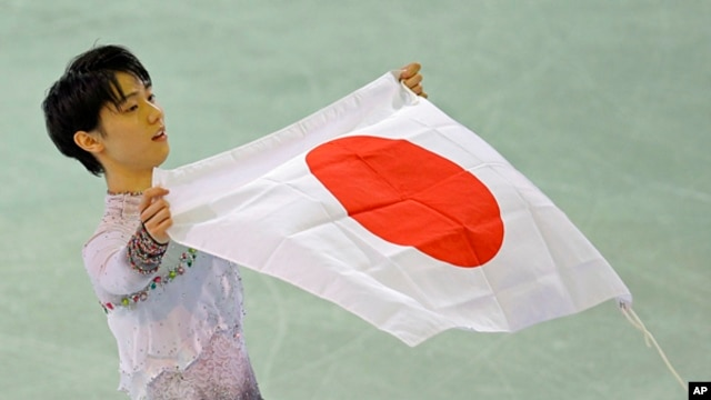 Yuzuru Hanyu of Japan poses with the national flag after he placed first in the men's free skate figure skating final following the flower ceremony at the Iceberg Skating Palace during the 2014 Winter Olympics, Feb. 14, 2014, in Sochi, Russia.
