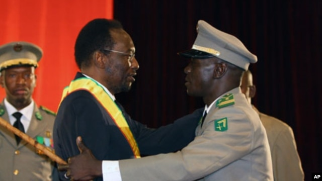 Mali's Interim President Dioncounda Traore (L) is congratulated by coup leader Amadou Sanogo after being sworn in at a ceremony in Bamako, Mali, April 12, 2012.