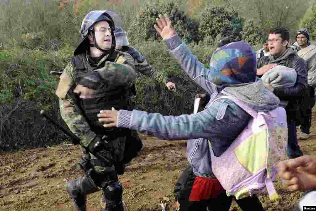A Macedonian policeman hits a stranded migrant attempting to cross the Greek-Macedonian border, near Gevgelija, Macedonia.