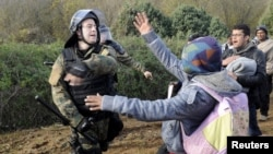 FILE - A Macedonian police officer hits a stranded migrant attempting to cross the Greek-Macedonian border, near Gevgelija, Macedonia, Dec. 2, 2015.
