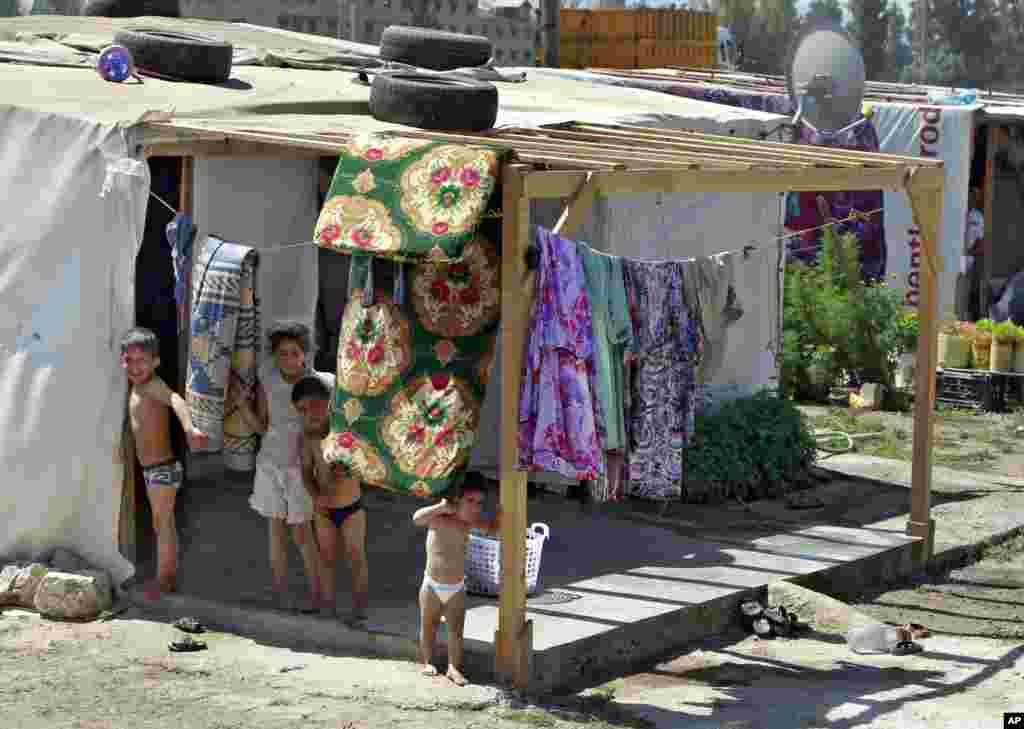 Syrian refugee children stand outside their tent, at a temporary refugee camp in the eastern Lebanese town of Faour near the border with Syria, August 28, 2013.