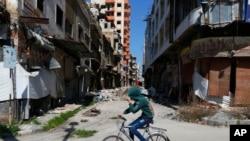 시리아 소년이 홈스에서 자전거를 타고 가고 있다.