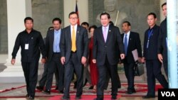 Cambodia's Priminister Hun Sen (R) with Sam Rainsy (L) president of the Cambodia National Rescue Party (CNRP) walk out of the National Assembly after voting for National Election Committee members, in Phnom Penh, Cambodia on April 9th, 2015. (Nov Povleakhena/VOA Khmer)