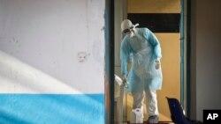 Un travailleur médical de l'unité de prévention et de contrôle des infections portant un équipement de protection complet décontamine une tasse utilisée par un homme en quarantaine, à l'hôpital national Kenyatta de Nairobi, au Kenya, le 8 octobre 2014.