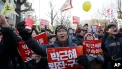 """Para pemrotes membawa spanduk bertuliskan """"Tahan Park Geun-hye"""" sambil meneriakkan slogan saat berpawai menuju kantor Presiden di Seoul, 10 Desember 2016 (AP Photo/Ahn Young-joon)."""