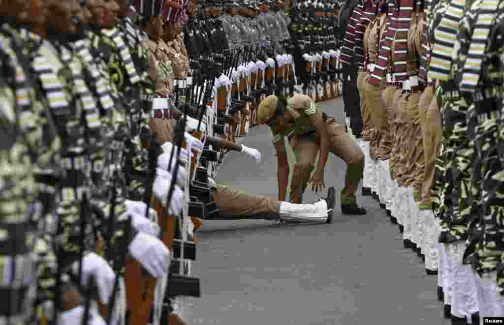An Indian policewoman helps her comrade who fainted during the full-dress rehearsal for India's Independence Day celebrations in the southern Indian city of Chennai. India commemorates its Independence Day on Aug. 15.