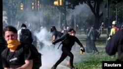 Seorang pengunjuk rasa mengembalikan tabung gas air mata saat berlangsungnya aksi unjuk rasa menentang kematian George Floyd, di Philadelphia, Pennsylvania, 1 Juni 2020.