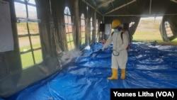 Petugas kesehatan menyemprotkan cairan disinfektan di tenda jelang pelaksanaan kegiatan psikososial di shelter Terintegrasi di Stadion Manakarra, Mamuju, Sulawesi Barat, Minggu, 31 Januari 2021. (Foto: Yoanes Litha/VOA)
