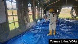 Petugas kesehatan menyemprotkan cairan disinfektan di tenda jelang pelaksanaan kegiatan pemulihan trauma di shelter Terintegrasi di Stadion Manakarra, Mamuju, Sulawesi Barat, Minggu, 31 Januari 2021. (Foto: Yoanes Litha/VOA)