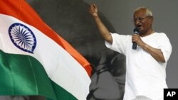 Indian social activist Anna Hazare gestures while addressing his supporters on the tenth day of his protest fast as an India's national flag flutters at the Ramlila grounds in New Delhi, August 25, 2011.