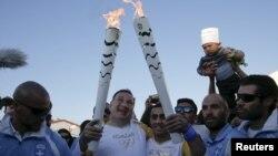 Le président du Comité olympique passe la flame au réfugié syrien Ibrahim Al-Hussein à Athènes, le 26 avril 2016.