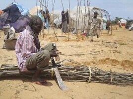 A man from drought-stricken southern Somalia cuts tree branches to construct a makeshift shelter in refugee camp in the capital, Mogadishu.
