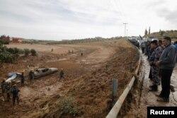 Warga setempat menyaksikan anggota pertahanan sipil melakukan pencarian korban pasca badai yang memicu banjir bandang, di kota Madaba, dekat Amman, Yordania, (10/11).