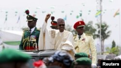 Nigeria's new President Muhammadu Buhari rides on the motorcade while inspecting the guard of honor at Eagle Square in Abuja, Nigeria, May 29, 2015.