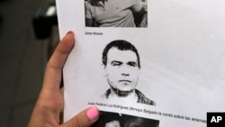 "FILE- A reporter holds a picture of Antonio ""Jaime"" Stiusso, one of the country's most enigmatic spy chiefs, outside the prosecutor's office in Buenos Aires, Feb. 5, 2015."