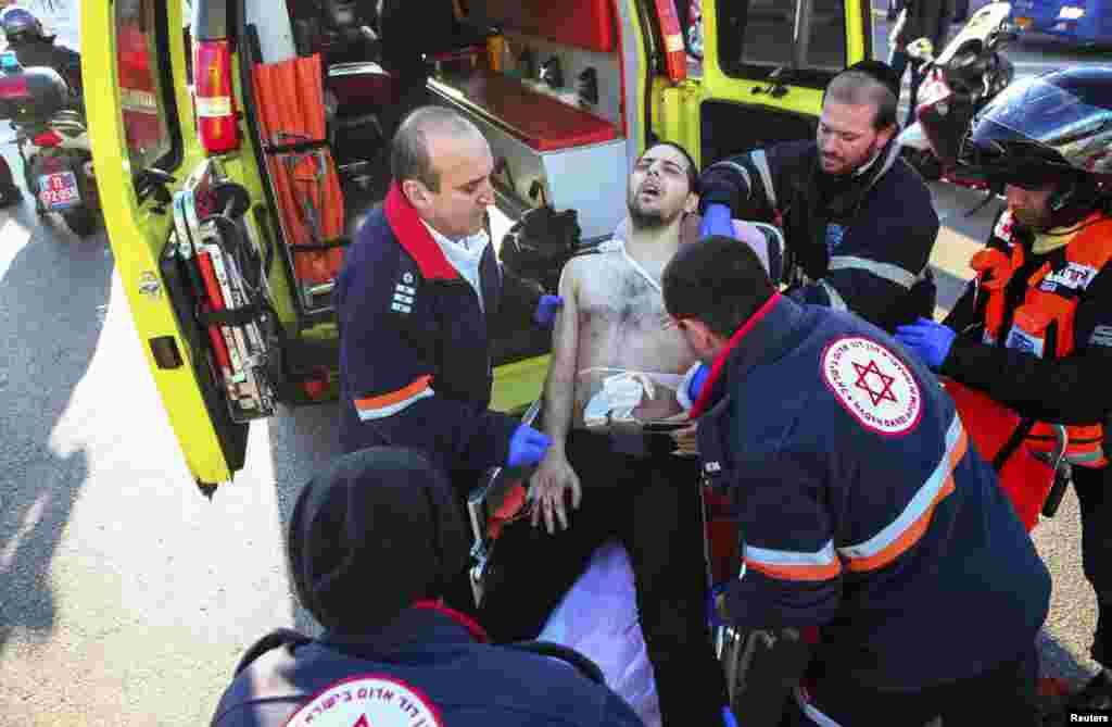 امدادگران اسرائيلی در محل حادثه در تل آويو مرد مضروبی را به آمبولانس منتقل می کنند-- ۱ بهمن ۱۳۹۳ (۲۱ ژانويه ۲۰۱۵)
