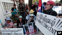 Boeung Kak lake community's land activists shout slogans with a poster of detained Tep Vanny during a rally in front of an appeals court in Phnom Penh, Cambodia, Tuesday, Aug. 8, 2017. The court upheld a 2 ½ year prison term against Tep Vanny, a prominent land rights activist on charges of committing violence at a protest she helped lead outside of Prime Minister Hun Sen's residence more than three years ago. (AP Photo/Heng Sinith)