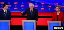 ete Buttigieg (L) and U.S. Senator Elizabeth Warren (R) watch U.S. Senator Bernie Sanders