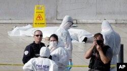Polisi Penyidik sedang bekerja di samping jenazah yang ditutupi kain putih di luar stasiun kereta Marseille, di Marseille, selatan Perancis, 1 Oktober 2017.