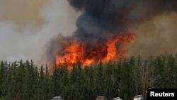 Un feu de forêt brûle pendant que des personnes évacuées ont été bloqués au nord de Fort McMurray, en Alberta sur la route 63 , le 6 mai 2016