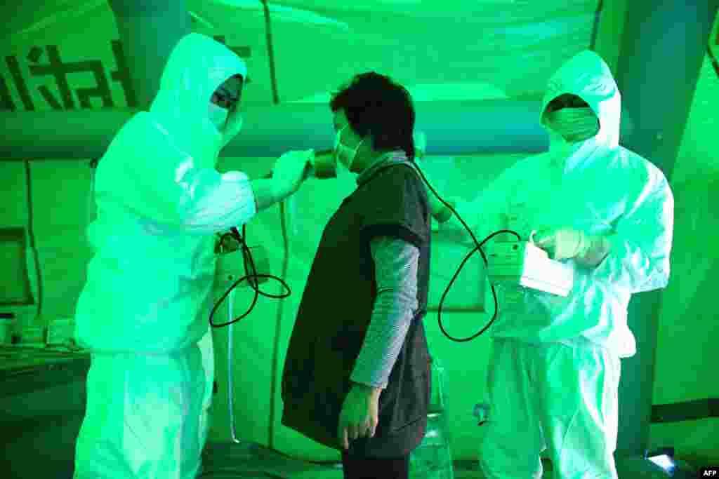 Медицинский персонал использует счетчик Гейгера для проверки возможного радиационного воздействия, Хитачи, Япония, 16 марта 2011г.