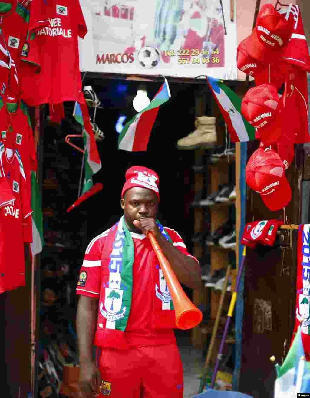 Um homemtodo equipado com as cores da Guiné Equatorial exibe as t-shirts, bandeiras, cachecóis e vuvuzelas à venda na sua loja em Bata. Jan 16, 2015