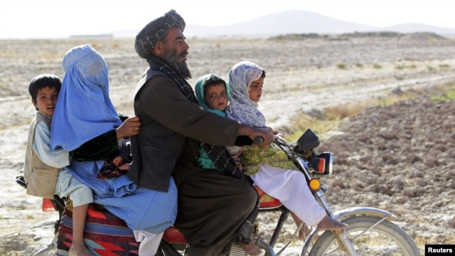Cư dân lái xe gắn máy trên một con đường trong tỉnh Helmand, tây nam Afghanistan, ngày 8/11/2012.