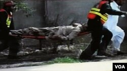 Regu penyelamat membawa korban bom di Peshawar, Pakistan, 5 April 2010.
