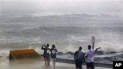 People stand at the end of a street looking at a stormy Atlantic Ocean as Hurricane Irene arrives, in Cape May, New Jersey, August 27, 2011