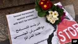 "A banner with flowers is placed on the steps to the Cologne cathedral reading in English and Arabic ""sexual harassment against women will not be tolerated"", New Year's Eve sexual assaults and robberies in Cologne were blamed largely on foreigners. (AP Photo/Martin Meissner)"