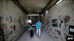 Omar Hajajla, warga Palestina berjalan dengan putranya melalui terowongan yang menghubungkan rumah mereka di Yerusalem ke al-Walajah, desa mereka di Tepi Barat, 30 Mei 2019. (Foto: AFP)