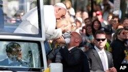El papa Francisco besa a un bebé a su paso por una calle de Washington, en la Alameda Nacional.