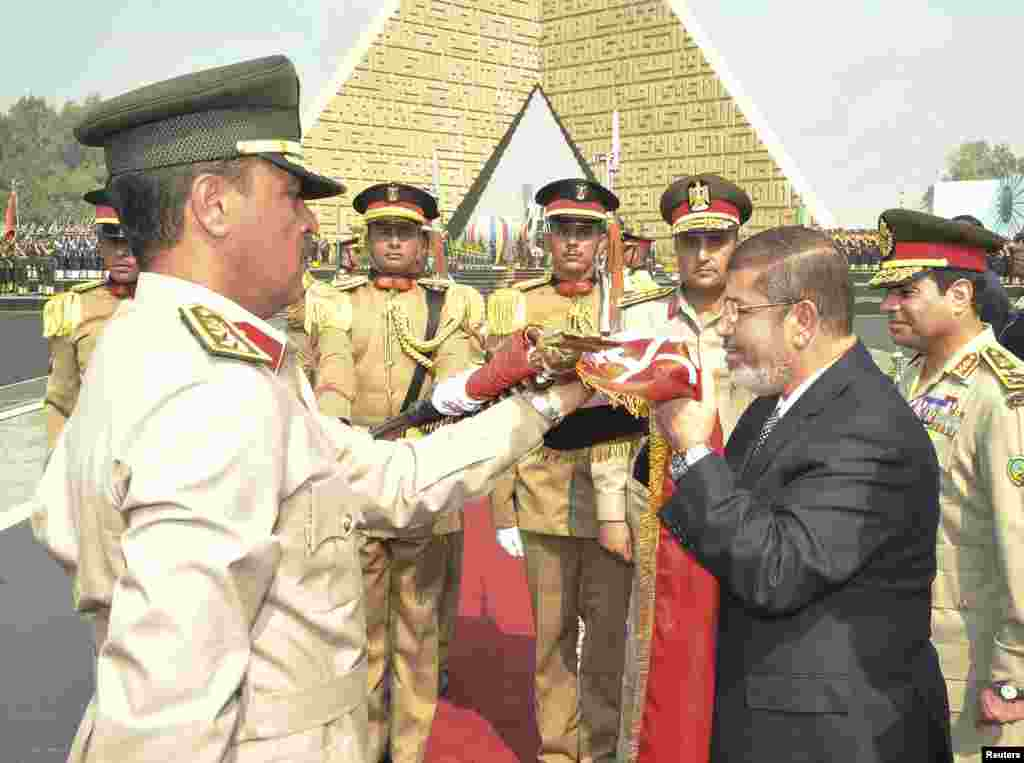 Egypt's President Mohamed Mursi (2nd R) kisses the national flag during his visit to the tomb of former President Anwar al-Sadat for the anniversary of Egypt's October 6, 1973 surprise attack, in Cairo October 4, 2012.