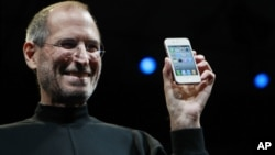 FILE - Apple CEO Steve Jobs smiles with a new iPhone at the Apple Worldwide Developers Conference in San Francisco. In the white-hot competition for tech talent, some workers are alleging Silicon Valley's top companies conspired to keep employees from switching teams, June 7, 2010.