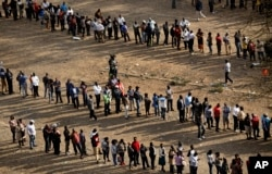 FILE - Kenyans queue to cast their votes at dusk at a polling station in downtown Nairobi, Aug. 8, 2017.