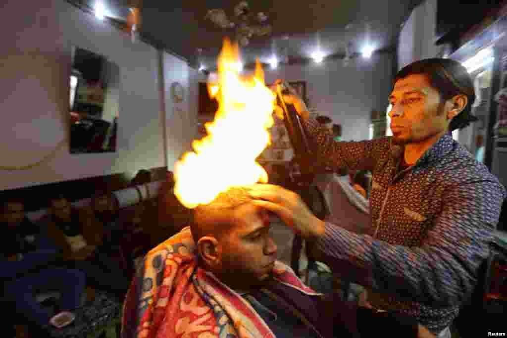 Tukang cukur Palestina, Ramadan Odwan, meluruskan dan membentuk rambut pelanggannya dengan api di salonnya di Rafah, Jalur Gaza.