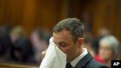 Oscar Pistorius essuie ses larmes lors du prononcé de sa condamnation pour le meurtre de sa copine au tribunal de Pretoria, Afrique du Sud, 17 octobre 2014.