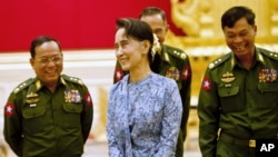 Myanmar's NLD party leader Aung San Suu Kyi smiles with army members during the handover ceremony of outgoing President Thein Sein and new President Htin Kyaw at the presidential palace in Naypyitaw, March 30, 2016.