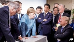 In this photo made available by the German Federal Government, German Chancellor Angela Merkel, center, speaks with U.S. President Donald Trump, seated at right, during the G7 Leaders Summit in La Malbaie, Quebec, Canada, on Saturday, June 9, 2018