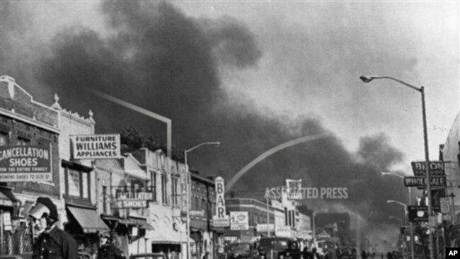 资料图片 - 在密歇根州底特律爆发种族骚乱后,底特律警方检查了距离密歇根州底特律市中心约3英里的第12街沿线的建筑物。许多商店和房屋被烧毁和抢劫。(1967年7月24日,)(美联社照片)