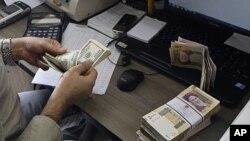 Một nhân viên phòng giao hoán đếm các tờ đôla Mỹ, trên bàn là xấp giấy bạc Iran