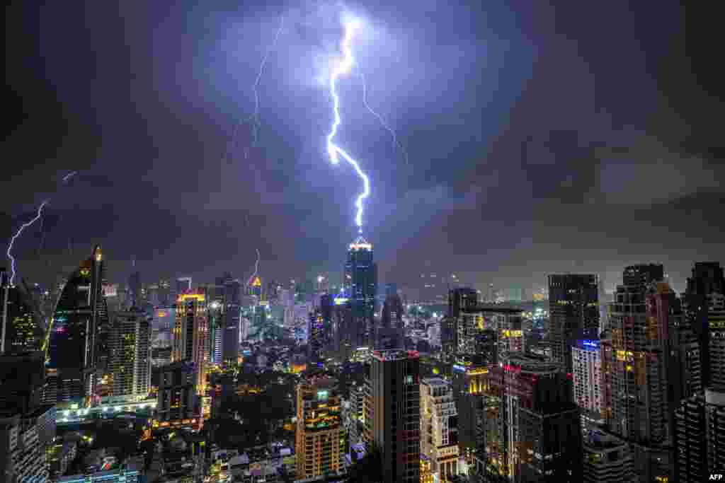 Lightening strikes on a building during a thunderstorm in Bangkok, Thailand.
