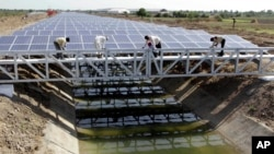 FILE - Indian workers add finishing touches to installed solar panels covering the Narmada canal at Chandrasan village, about 40 kilometers from Ahmadabad, India, April 22, 2012.
