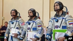 Russian cosmonauts Anton Shkaplerov (C) and Anatoly Ivanishin (R), and U.S. astronaut Daniel Burbank walk together after completing exams at the Star City space center outside Moscow, September 2, 2011