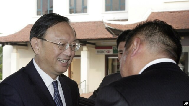 Chinese State Councilor Yang Jiechi, left, is greeted by a hotel executive as he arrives in Hanoi, Vietnam, June 17, 2014.