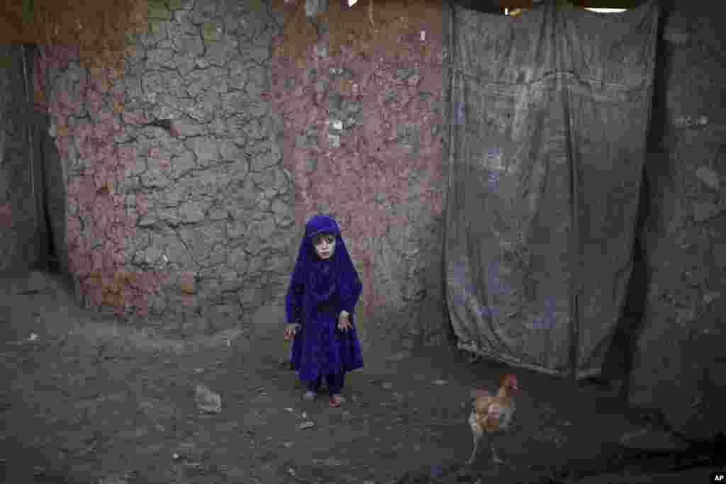 اسلام آباد ته نژدې په یوه فقیره ټولنه کې یو افغان مهاجر ماشوم د خپل خټین کور په مخ کې.