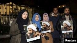 manifestantes exibem cartazes com a imagem de Nimr al-Nimr
