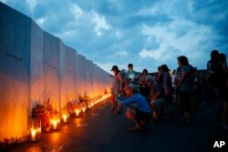 Candles in memory of the passengers and crew of Flight 93, are lit along the Wall of Names at the Flight 93 National Memorial in Shanksville, Pa., Sept. 10, 2016, as the nation marks the 15th anniversary of the Sept. 11 attacks.